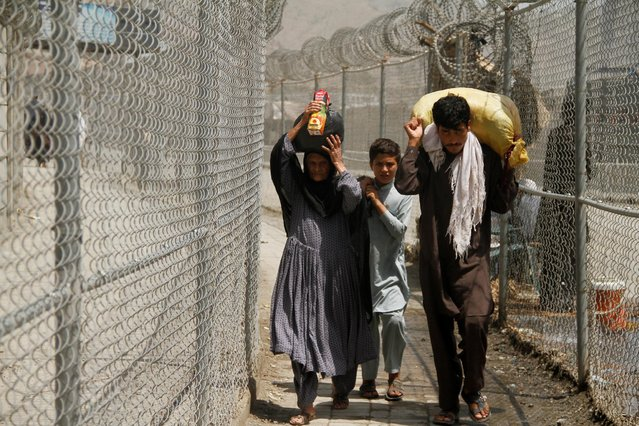 A family coming from Afghanistan walk down a corridor between security fences at the border post in Torkham, Pakistan June 18, 2016. (Photo by Fayaz Aziz/Reuters)
