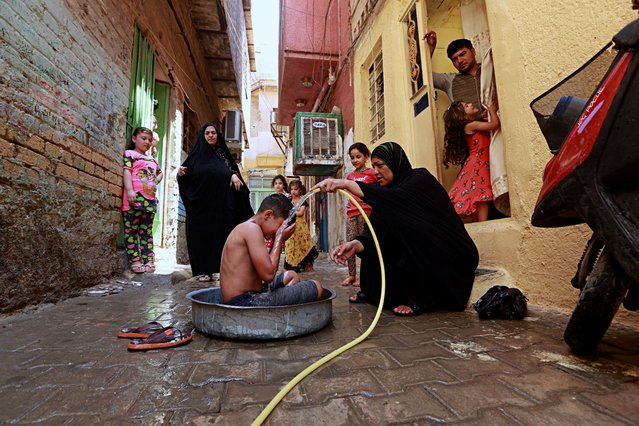 In this photo taken on Friday, July 28, 2017, Umm Ali gives her son a bath to beat the heat in the poor neighborhood of Fadhil in Baghdad, Iraq. Iraq's weather service warned Thursday that temperatures will increase next week in most parts of the country, with the highs expected to reach 51 degrees Celsius, or about 124 degrees Fahrenheit, adding to the daily woes of Iraqi citizens already facing a deteriorated security situation and lack of public services. (Photo by Hadi Mizban/AP Photo)