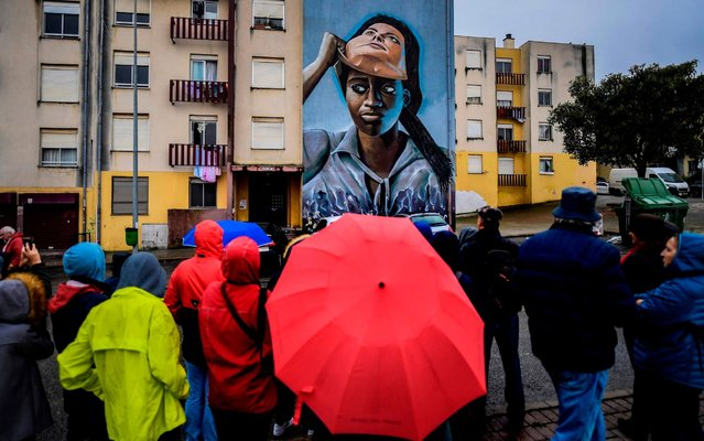 Visitors watch a mural by Portuguese artist Nomen during a guided visit to Quinta do Mocho neighbourhood in Sacavem, outskirts of Lisbon, on November 11, 2019. The image of a black woman removing her white-woman mask is one of the hundreds of murals that cover the buildings of the underprivileged district of Quinta de Mocho in Lisbon, that has been transformed by street art. (Photo by Patricia De Melo Moreira/AFP Photo)
