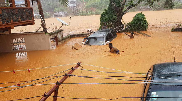 This handout picture released on August 14, 2017, by Society 4 Climate Chnage Communication Sierra Leone, shows flooded streets in Regent near Freetown. The death toll from massive flooding in the Sierra Leone capital of Freetown climbed to 312 on August 14, 2017, the local Red Cross told AFP. Red Cross spokesman Patrick Massaquoi told AFP the toll could rise further as his team continued to survey disaster areas in Freetown, where heavy rains have caused homes to disappear under water and triggered a mudslide. (Photo by /AFP Photo/Society 4 climate change communication Sierra Leone)