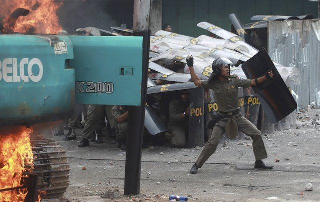 A municipal police officer throws a stone back at protesting residents of Kampung Pulo after clashes erupted during an eviction in Jakarta, Indonesia, August 20, 2015 in this photo taken by Antara Foto. Residents facing eviction from a flood-prone part of Indonesia's capital of Jakarta clashed with police on Thursday, prompting security forces to fire tear gas and water cannon. (Photo by Muhammad Adimaja/Reuters/Antara Foto)