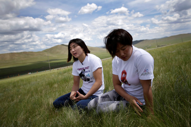 Mongolia's Olympic wrestler Battsetseg Soronzonbold (L) and her teammate Sumiya Erdenechimeg are seen during an interview with Reuters on the grasslands after a daily training session outside the Mongolia Women's National Wrestling Team training centre in Bayanzurkh district of Ulaanbaatar, Mongolia, July 1, 2016. (Photo by Jason Lee/Reuters)