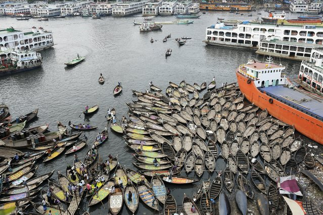 Boatmen wait in the polluted water near the river bank of Buriganga on the eve of World Environment Day, in Dhaka, Bangladesh, 04 June 2017. A large swathe of the Buriganga River which is the lifeline of the capital has turned pitch-black with toxic waste, oil and chemicals flowing into it from industrial units. The water became extremely polluted and represents a health hazard for the riverbed communities. (Photo by Abir Abdullah/EPA)