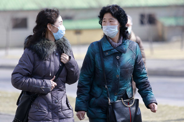 People wear masks to protect from a new coronavirus as they walk through the Kwangbok Street in Pyongyang, North Korea Wednesday, February 26, 2020. Uncertainly remained over how best to stem the spread of the illness. (Photo by Jon Chol Jin/AP Photo)