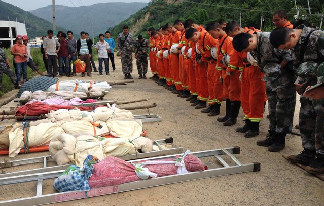 Rescuers (R) bow as they pay tribute to residents who were killed during an earthquake in Longtoushan township of Ludian county, Yunnan province August 4, 2014. A magnitude 6.3 earthquake struck southwestern China on Sunday, killing at least 398 people in a remote area of Yunnan province, and causing thousands of buildings, including a school, to collapse. (Photo by Reuters/Stringer)
