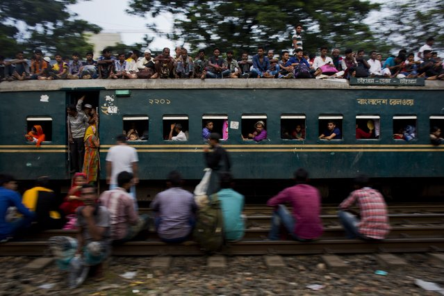 Bangladeshi Muslims travel on the roof of an overcrowded train as they head to their hometowns ahead of Eid al-Adha in Dhaka, Bangladesh, Friday, September 1, 2017. The festival commemorates the story of Abraham and his readiness to sacrifice his son as an act of obedience to God, who provided a lamb to be used instead. (Photo by Bernat Armangue/AP Photo)