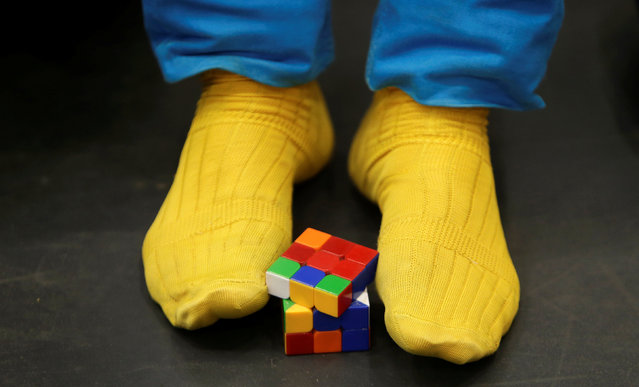 A competitor solves a Rubik's cube using his feet as he prepares for the Rubik's Cube European Championship in Prague, Czech Republic, July 15, 2016. (Photo by David W. Cerny/Reuters)
