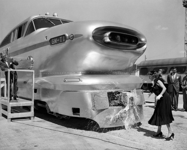 """N.C. Dezendorf, wife of the general manager of the Electro-Motive division of General Motors, christens the new lightweight """"Aerotrain"""" at the company's locomotive works in La Grange, Ill. on August 22, 1955. (Photo by Edward Kitch/AP Photo)"""