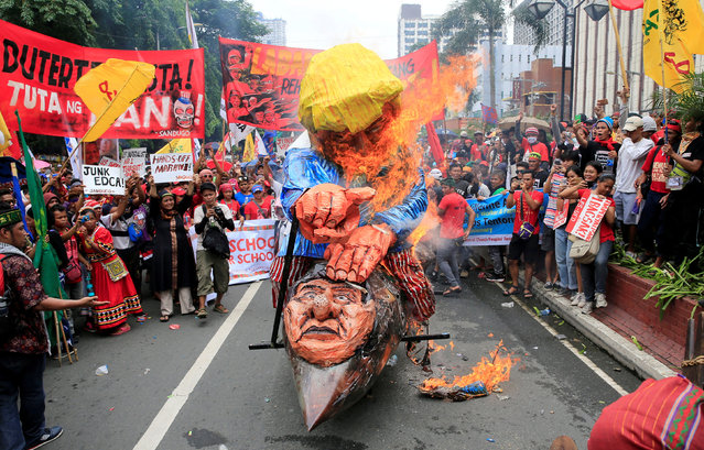Protesters burn effigies of U.S. President Donald Trump and Philippine President Rodrigo Duterte to express their outrage over what they say is the increasing intervention of the United States in the ongoing war in Marawi city, southern Philippines, during a protest outside the U.S. embassy in metro Manila, Philippines September 15, 2017. (Photo by Romeo Ranoco/Reuters)