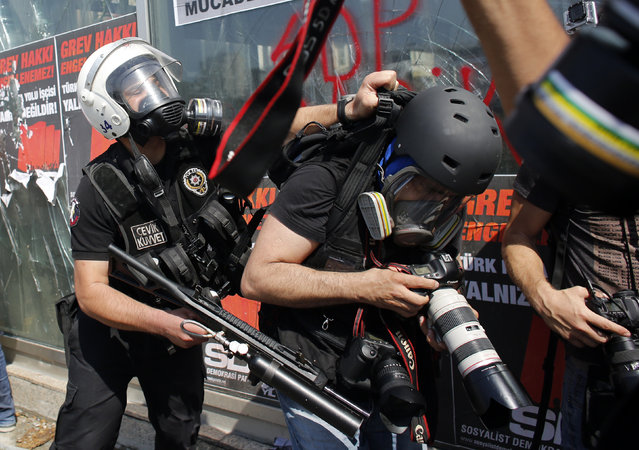 A Turkish riot policeman pushes a photographer during a protest at Taksim Square in Istanbul June 11, 2013. (Photo by Murad Sezer/Reuters)