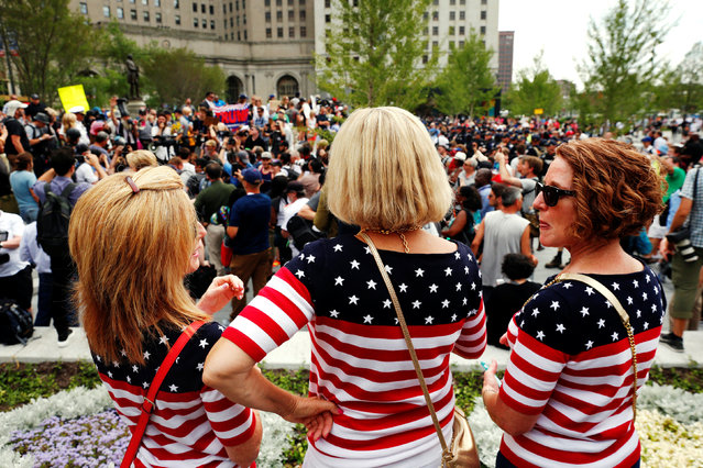 Women wearing U.S. flag themed shirts watch demonstrators near the Republican National Convention in Cleveland, Ohio, U.S., July 21, 2016. (Photo by Lucas Jackson/Reuters)
