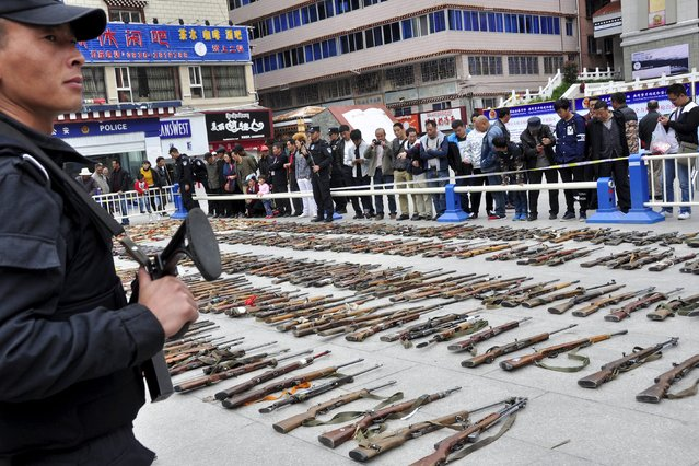 A policeman (L) stands guard next to illegal weapons confiscated by authorities during a massive destruction event in Garze Tibetan Autonomous Prefecture, Sichuan province, China, September 1, 2015. According to local media, police in the prefecture has seized as many as 3,410 guns, 133,207 bullets, 18,002 kilograms of explosives and 2,521 knives since 2011. (Photo by Reuters/Stringer)