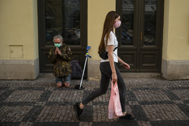 A woman walks past a beggar as both are wearing a face mask on April 19, 2020 in Prague, Czech Republic amid restrictions due to the new coronavirus COVID-19 pandemic. (Photo by Michal Cizek/AFP Photo)
