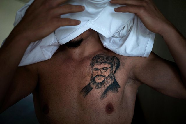 "In this Tuesday, May 24, 2016 photo, Tayseer, 30, civil servant, covers his face as he poses for a photo showing a tattoo of Hezbollah leader Hassan Nasrallah, in the southern suburb of Beirut, Lebanon. He got it five months ago as an expression of ""deep love"" for the man he says is protecting Lebanon from Islamic State group and other extremists fighting in neighboring countries. (Photo by Hassan Ammar/AP Photo)"