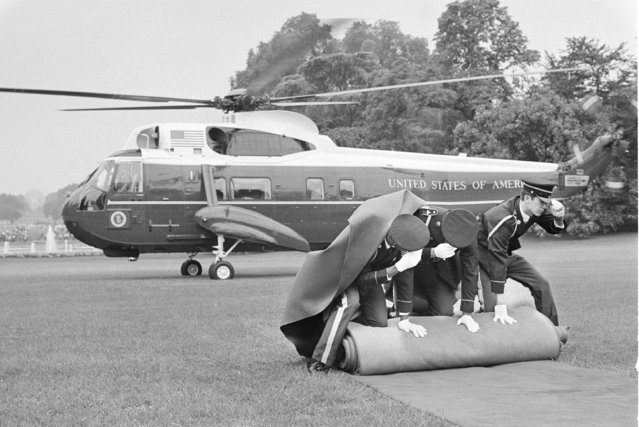 Member of the honor guard hold down the red carpet as the helicopter carrying Richard M. Nixon from the White House prepares to lift off from the grounds on Friday, August 9, 1974. After a farewell speech to members of the White House staff Nixon departed for California. (Photo by AP Photo)
