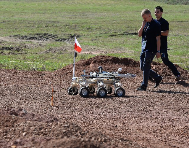 "Members of the  Kielce University of Technology  team, watch their ""Impuls"" Mars rover before the European Rover Challenge 2014 on September 5, 2014 in Checiny, Poland. (Photo by Janek Skarzynski/AFP Photo)"