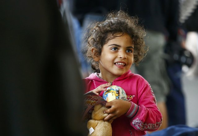 A migrant girl stands with her teddy bear at a railway station in Vienna, Austria September 5, 2015. (Photo by Dominic Ebenbichler/Reuters)