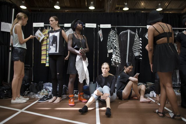 """Hedvig Palm of Sweden, center, sits on the floor backstage before she models the DKNY Spring 2015 collection Sunday, September 7, 2014, during Fashion Week in New York. This is Palm's seventh season modeling. Asked if she misses home, Palm said """"Sometimes when I hear a song...I think of my family. I hear a song and I want to be with my friends and family and be comfortable"""". (Photo by John Minchillo/AP Photo)"""