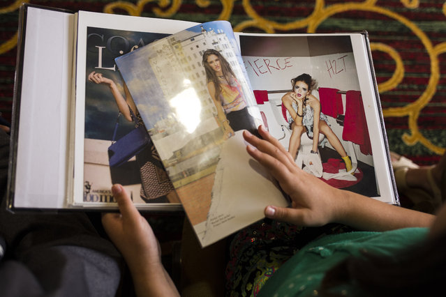 Camp attendees pass around the portfolio book of Victoria Henley, formerly of Americas Next Top Model, at a modeling camp at the Courtyard Marriott Hotel in McLean, Va., on Tuesday, August 18th, 2015. (Photo by Brittany Greeson/The Washington Post)
