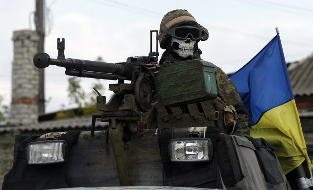 A Ukrainian serviceman rides on an armoured vehicle near the eastern Ukrainian town of Debaltseve, September 23, 2014. (Photo by David Mdzinarishvili/Reuters)