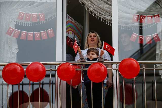 Local residents, in their flat due to the coronavirus, watch celebrations ahead of the National Sovereignty and Children's Day, in Istanbul, Wednesday, April 22, 2020. Turkey will mark Thursday, April 23, 2020 the 100th anniversary of the foundation of its parliament, as the nation is in a 4-day curfew declared by Turkey's government in an attempt to control the spread of the COVID-19 pandemic. (Photo by Emrah Gurel/AP Photo)