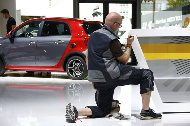 An employee works in front of a Smart forfour car during the media day at the Frankfurt Motor Show (IAA) in Frankfurt, Germany, September 14, 2015. (Photo by Ralph Orlowski/Reuters)