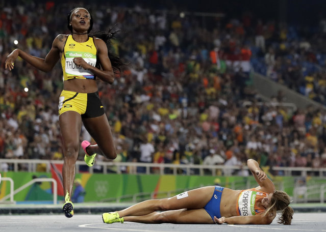 Second placed Netherlands' Dafne Schippers lies on the ground after falling over the finish line as Elaine Thompson from Jamaica, left, wins the gold in the women's 200-meter final during the athletics competitions of the 2016 Summer Olympics at the Olympic stadium in Rio de Janeiro, Brazil, Wednesday, August 17, 2016. (Photo by David J. Phillip/AP Photo)