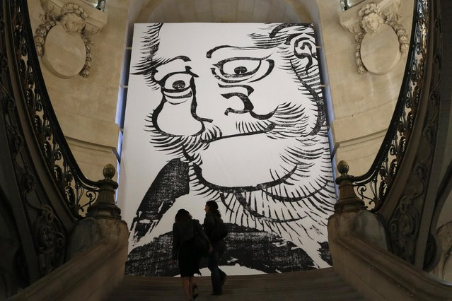 "Journalists walk up a staircase during press day for the opening of the exhibition ""Hokusai (1760-1849)"", the Japanese artist who lived from 1760 until 1849, near a partial reproduction of the poster ""Daruma"" which dates from 1817 at the Grand Palais in Paris September 29, 2014. (Photo by John Schults/Reuters)"