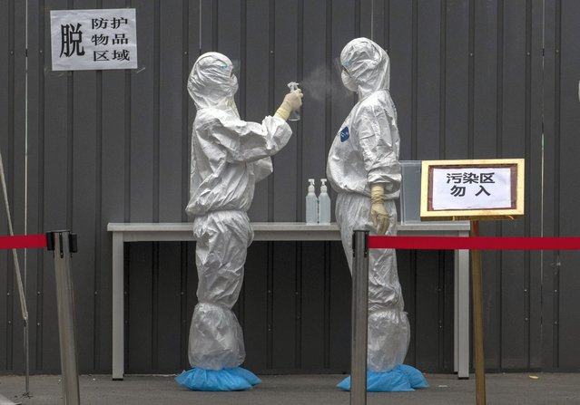 Chinese epidemic control workers wear protective suits as they disinfect each other after performing nucleic acid swab test for COVID-19 on citizens at a government testing site in Xicheng District during an organized tour on June 24, 2020 in Beijing, China. While Chinese government medical officials have said they believe they have controlled the spread, authorities are trying to contain the outbreak linked to the Xinfadi wholesale food market, Beijing's biggest supplier of produce and meat. More than 2.5 million people have undergone nucleic acid tests for COVID-19 at dozens of sites across the city in recent days, with officials using contact tracing to target high and middle risk areas and people who may have had contact with the market or food that came from there. Several neighborhoods have been locked down and a number of other food markets have been closed, The outbreak has triggered fears of a second wave of infection after 56 straight days with no domestically transmitted cases in the capital. (Photo by Kevin Frayer/Getty Images)