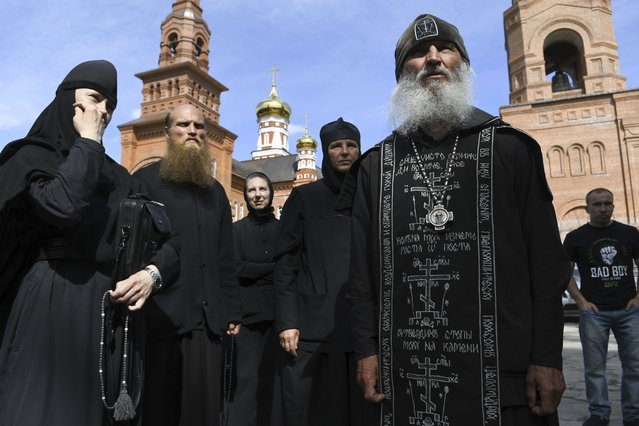 Father Sergiy, a Russian monk who has defied the Russian Orthodox Church's leadership, right, speaks to journalists in Russian Ural's Sredneuralsk, Russia, Wednesday, June 17, 2020. The monk, who has denied the coronavirus' existence and urged believers to ignore the Kremlin's lockdown orders, has taken control of a monastery in the Ural Mountains. (Photo by Vladimir Podoksyonov/AP Photo)