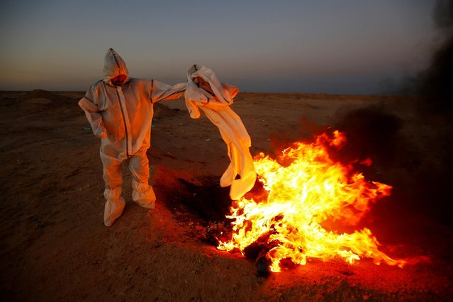 A member of the Popular Mobilization Forces (PMF), who volunteered to work in a cemetery, wears a protective suit, as he burns clothes they used for burial, near the new Wadi Al-Salam cemetery, which is dedicated to those who died of the coronavirus disease (COVID-19), on the outskirts of the holy city of Najaf, Iraq on May 25, 2020. (Photo by Alaa al-Marjani/Reuters)