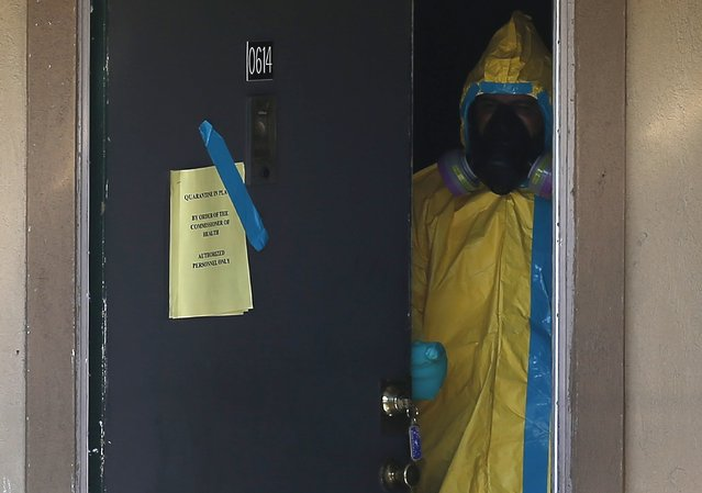 A worker in a hazardous material suit looks out from the apartment unit where a man diagnosed with the Ebola virus was staying in Dallas, Texas, October 5, 2014. Thomas Eric Duncan, the first person diagnosed with Ebola in the United States, was fighting for his life at a Dallas hospital on Sunday and appeared not to be receiving any of the experimental medicines for the virus, a top U.S. medical official said. (Photo by Jim Young/Reuters)