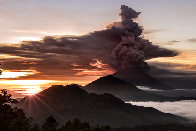 Mount Agung volcano is seen spewing smoke and ash in Bali, Indonesia, November 26, 2017 in this picture obtained from social media. (Photo by Emilio Kuzma-Floyd/Reuters)