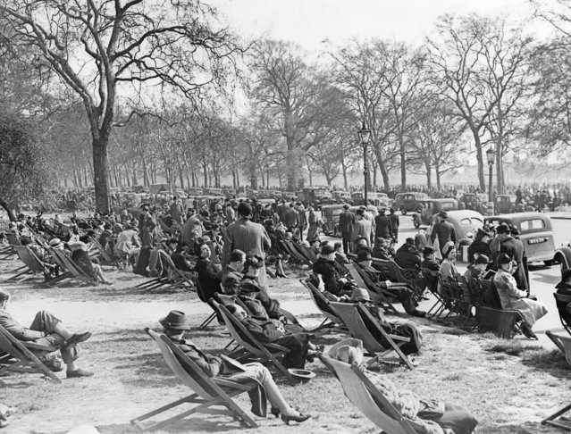 """Automobiles line a roadside through Hyde Park, London, on May 4, 1941, the sunshine attracting  crowds despite the threat of air raids. This is part of the crowd that caused seat ticket-sellers to report """"capacity business"""". (Photo by AP Photo)"""