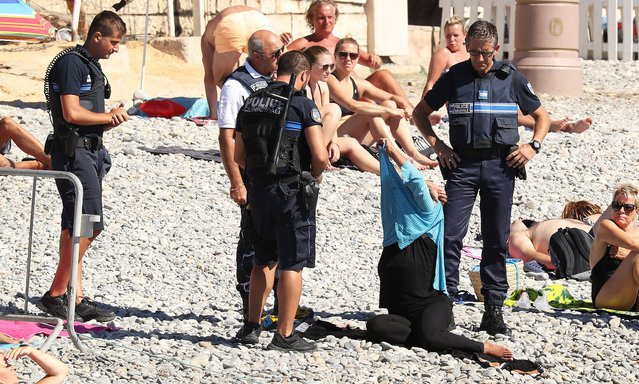 Police patrolling the Promenade des Anglais beach in Nice, France on August 24, 2016, fine a woman for wearing a burkini. (Photo by VantageNews.com)