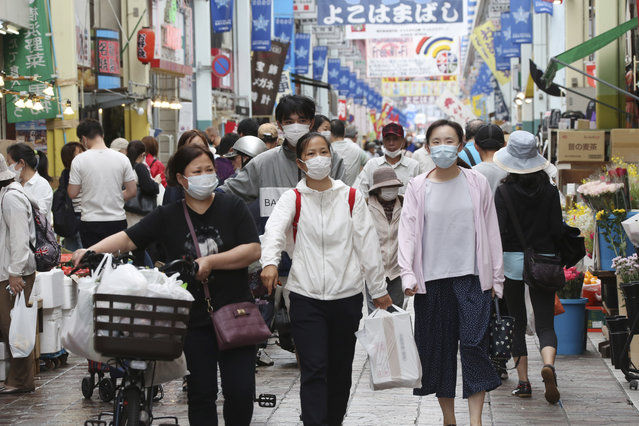 People wearing face masks shop at a mall in Yokohama, near Tokyo, Tuesday, June 23, 2020. Japan's economy is opening cautiously, with social-distancing restrictions amid the coronavirus pandemic. (Photo by Koji Sasahara/AP Photo)