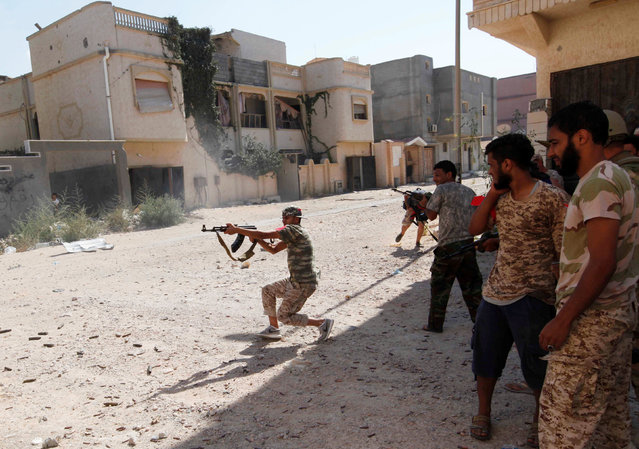 A member of Libyan forces allied with the UN-backed government fires a weapon towards Islamic State militants in neighbourhood Number One in central Sirte, Libya August 28, 2016. (Photo by Ismail Zitouny/Reuters)