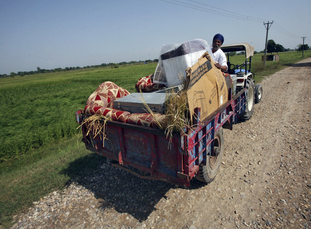 "A man with his belongings on a tractor cart moves to a safer place at Jagowal village near Jammu October 9, 2014. India warned Pakistan it would pay an ""unaffordable price"" if it persisted with shelling and machine-gun fire across a heavily populated border area in the lowlands of Kashmir, raising the stakes in the rivals' worst fighting in more than a decade. (Photo by Mukesh Gupta/Reuters)"