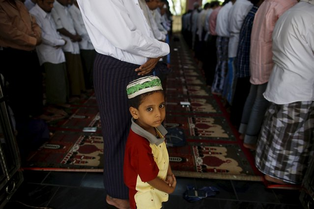 A boy stands next to Muslims performing the Eid al-Adha prayer at a mosque in Yangon, Myanmar September 25, 2015. (Photo by Soe Zeya Tun/Reuters)