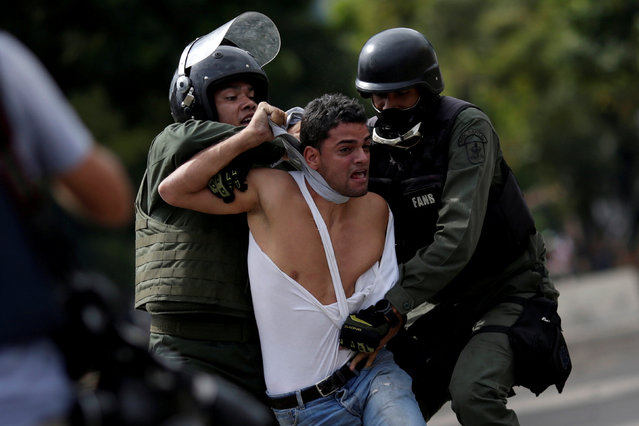 """A demonstrator is detained at a rally during a strike called to protest against Venezuelan President Nicolas Maduro's government in Caracas, Venezuela, July 27, 2017. Ueslei Marcelino: """"As the young protestor realised that he was being arrested he began to shout his name. I think that he hoped he could warn his relatives through people who were there and maybe through the press"""". (Photo by Ueslei Marcelino/Reuters)"""