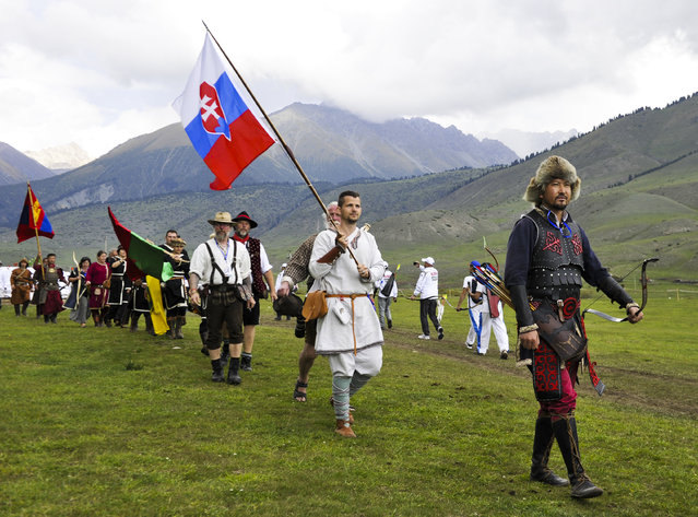 In this photo taken on Sunday, September 4, 2016, Slovakian, right, and Mongolian, left, and participants from other countries attend the second World Nomad Games at Issyk Kul lake in Cholpon-Ata, Kyrgyzstan. (Photo by Vladimir Voronin/AP Photo)