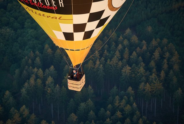 A hot-air balloon flies above a forest in Arnsberg, Germany, 08 September 2016. The mass start from the air field in Arnsberg is one of the highlights of the balloonists meeting Montgolfiade which continues until Saturday in Warnstein. (Photo by Bernd Thissen/EPA)