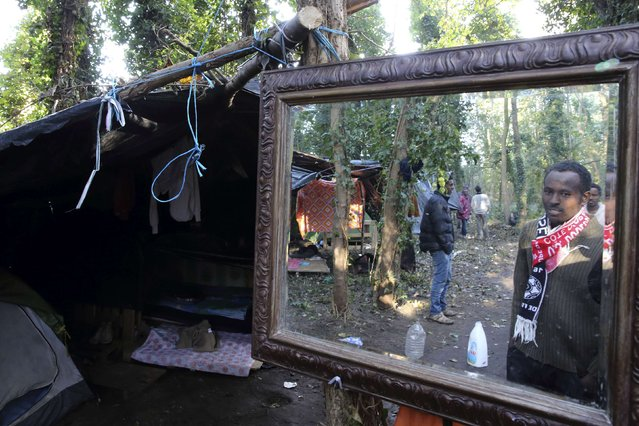 "An Ethiopian migrant is reflected in a mirror close to his makeshift shelter in the woods, known locally as the ""jungle"", near the harbour of Calais in northern France October 27, 2014. Roughly 2,300 immigrants, many of them from Africa, are roaming the streets and sleeping in makeshift camps in and around Calais while waiting to attempt the final leg of their bid to reach Britain, according to estimates from the local prefect's office. (Photo by Pascal Rossignol/Reuters)"