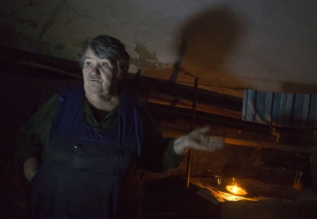 In this photo taken on Tuesday, October 21, 2014, Vera Dvornikova, a 70-year-old, whose home was destroyed in late July, hides from shelling in the basement under a hospital not far from Donetsk airport in the town of Donetsk, eastern Ukraine. (Photo by Dmitry Lovetsky/AP Photo)