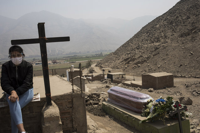 Janely Paccar, 23, sits near the coffin, at right, of her uncle Juan Paucar Quispe, 63, who died from COVID-19 complications, during his burial at a cemetery in Carabayllo, Lima, Peru, Tuesday, August 25, 2020. (Photo by Rodrigo Abd/AP Photo)