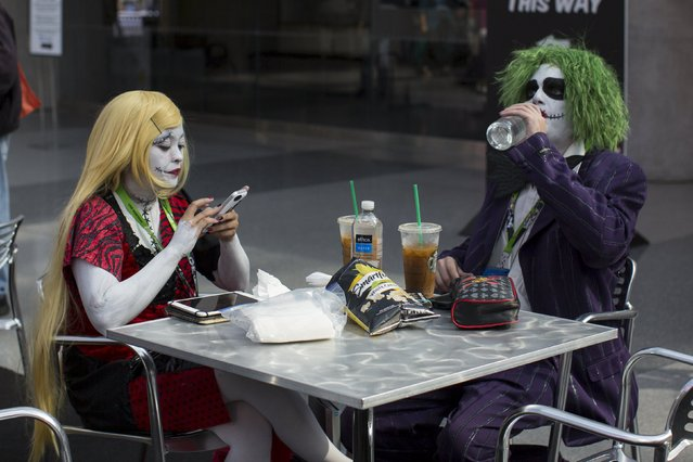 People dressed as Sally from Nightmare before Christmas and the Joker from Batman sit in the foodcourt at the New York Comic Con in Manhattan, New York, October 8, 2015. (Photo by Andrew Kelly/Reuters)