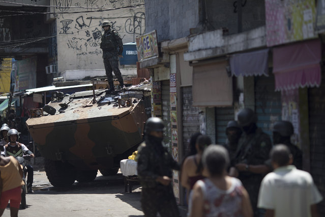 A soldier stands on top of an armored vehicle during a surprise operation in the Jacarezinho slum in Rio de Janeiro, Brazil, Thursday, January 18, 2018. (Photo by Leo Correa/AP Photo)