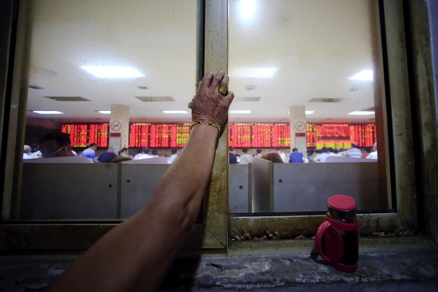 """Wang Fugui, wearing a gold ring and a bracelet, leans on a window at a smoking area of a brokerage house in Shanghai, China, September 7, 2015. Earlier this year, Wang earned and lost a big sum of money on the stock market which he believes was the value of """"a Mercedes car"""". (Photo by Aly Song/Reuters)"""