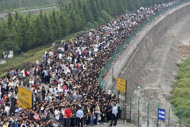 Visitors queue up before viewing the soaring tide near the bank of Qiantang River in Hangzhou, Zhejiang province September 25, 2010. Tidal waves are highest during the eighth month of the lunar calendar, local media reported. (Photo by Steven Shi/Reuters)