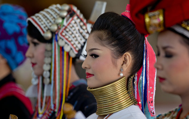 A woman in look-a-like ethnic Kayan-Padaung attire, with a fake copper neck ring, stands to welcome leaders attending the East Asia Summit at Myanmar International Convention Center in Naypyitaw, Myanmar, Thursday, November 13, 2014. Women welcoming world leaders stand in rows, colorfully clad in costumes representing Myanmar's many ethnic groups, some with their hair tied in high knots or wrapped in red headdresses, others donning horizontally striped longyis and silver coin-studded capes. (Photo by Gemunu Amarasinghe/AP Photo)